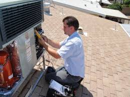 man fixing condenser on roof