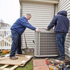 two men handling a condenser unit