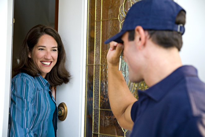 a service man talking to a woman at her door
