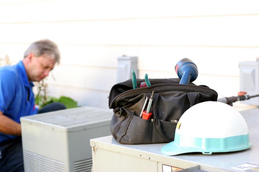 service man using tools to repaire air conditioner